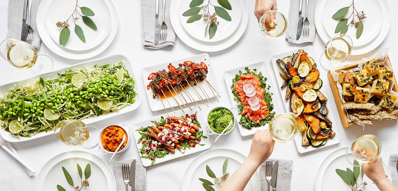Katettu ruokapöytä täynnä erilaisia herkkuja
